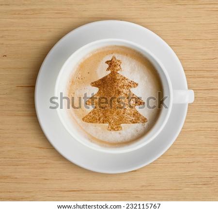 coffee cup with christmas tree shape on foam - stock photo
