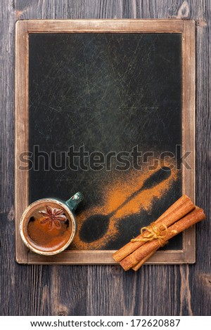 Coffee cup with cinnamon and star anise on vintage slate chalkboard - stock photo