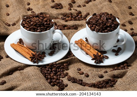 Coffee cup with coffee beans, cinnamon and aniseed. - stock photo