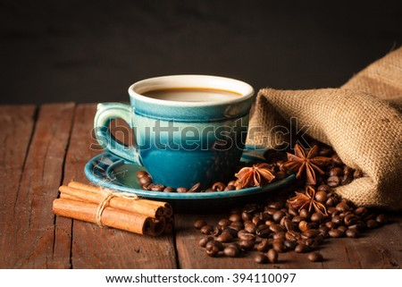 Coffee cup with coffee beans on wooden sacking background with anise and cinnamon - stock photo