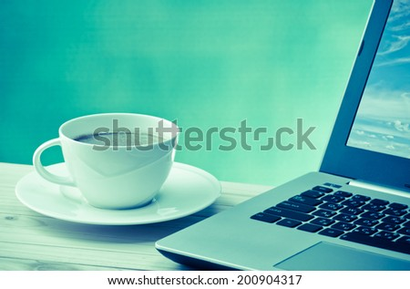 coffee cup with computer notebook on wood table with space for text in vintage color tone - stock photo