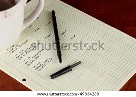 Coffee cup with general ledger sheet showing journal entries and black ballpoint pen on polished wooden table top - stock photo