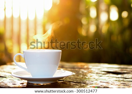 Coffee cup with hot coffee on old wood table in sunlight & blur green nature background - stock photo