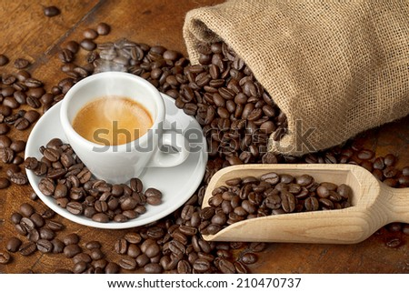 coffee cup with jute bag and spoon full of coffee beans - stock photo