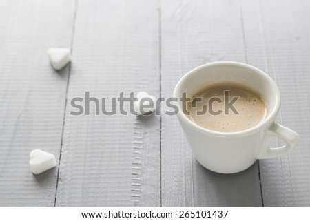 Coffee cup with milk and sugar cubes scattered - stock photo
