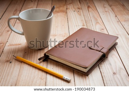 Coffee cup with notebook and pencil - stock photo