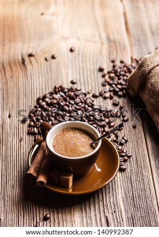 Coffee cup with roasted beans on rustic table - stock photo