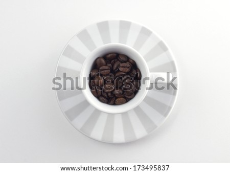 coffee cup with roasted beans on table - stock photo