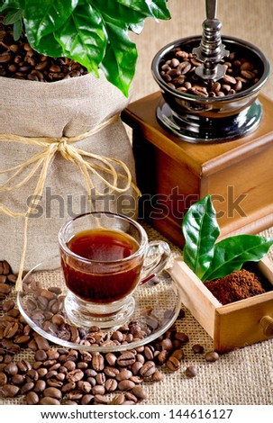 Coffee cup with saucer, coffee mill, bag with coffee tree and beans on the sackcloth - stock photo