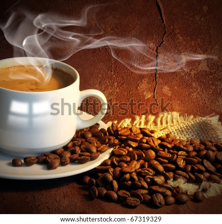 Coffee cup with smoke and grain against old wall. - stock photo