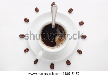 Coffee cup with spoon on saucer and coffee beans against white background forming clock dial. View from above. Coffee as symbol of morning energy and cheerfulness or evening refreshment. - stock photo