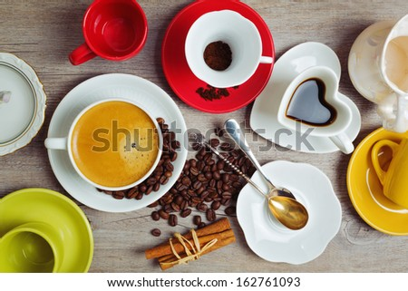 Coffee cups full and empty on wooden table. View from the top - stock photo