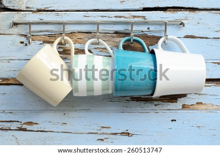 coffee cups hanging on old wood wall. - stock photo