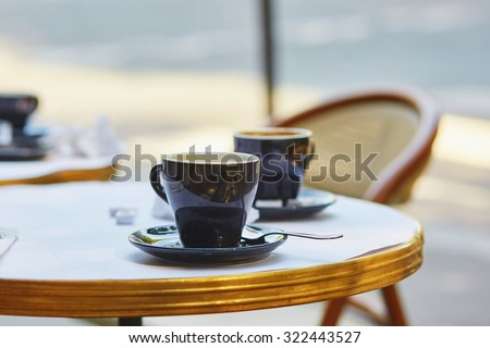 Coffee cups in an outdoor Parisian cafe - stock photo