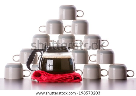 Coffee cups ready for refill neatly stacked into a pyramid shape on top of each other with a full carafe of freshly brewed filter coffee on a red cloth in front of them waiting to be dispensed - stock photo