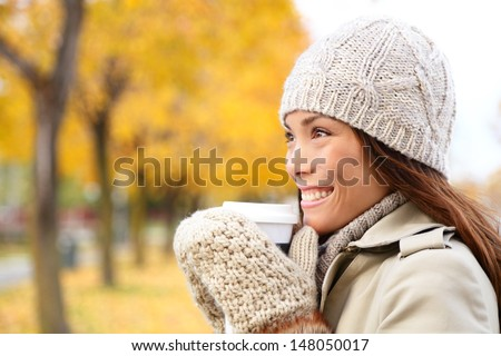 Coffee drinking woman in Autumn fall enjoying fall and hot drink from disposable cup. Smiling happy Asian female model in fall foliage. Mixed race Asian Chinese / Caucasian girl in her 20s. - stock photo