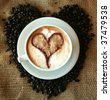 Coffee for Coffee Lovers, a cup of Coffee or  espresso with a Heart in the foam nestled in a bed of unground coffee beans on a burlap background - stock photo