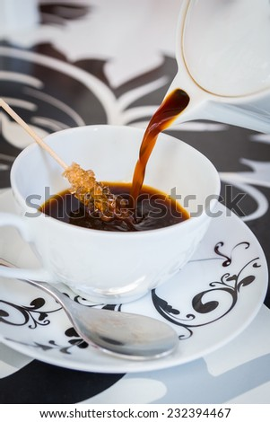 Coffee from a beautiful black and white teapot, pour into a cup on the table designer. Stick with sugar remain in the cup. Coffee, tea, mug, pour, caffe - the concept of catering. - stock photo