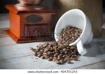 Coffee grain spill from a cup. Jute bag of roasted beans and mill in background - stock photo