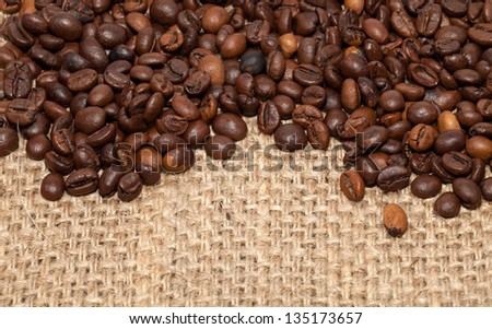 Coffee grains on rough fabric of linen close-up - stock photo