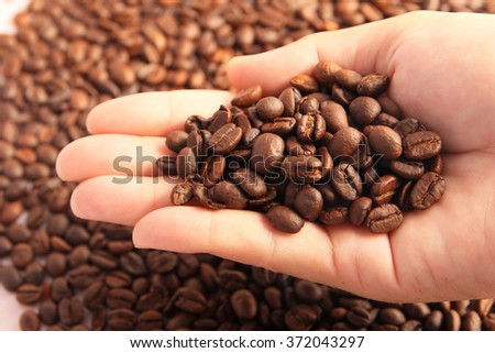 coffee grains on the hand - stock photo