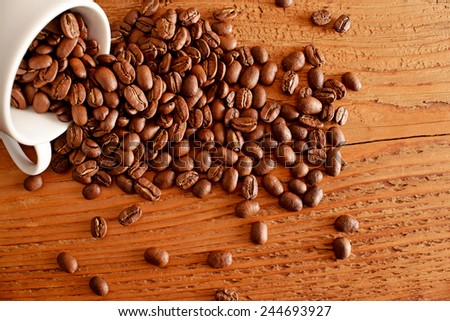 coffee grilled beans on old retro vintage aged yellow brown wooden table with a white cup on texture board table background Empty space for inscription  - stock photo
