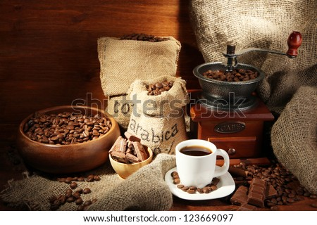 Coffee grinder and cup of coffee on brown wooden background - stock photo