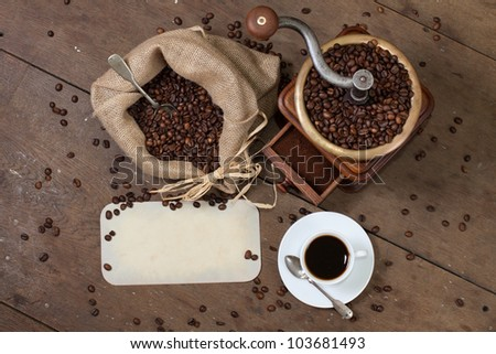 Coffee grinder (antique, XIX century), beans and silver spoon in canvas bag, cup, paper frame on the oak table - stock photo