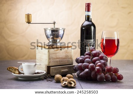 Coffee grinder, coffee and sweet Italian cookie cantuccini, grapes and glass of wine - stock photo