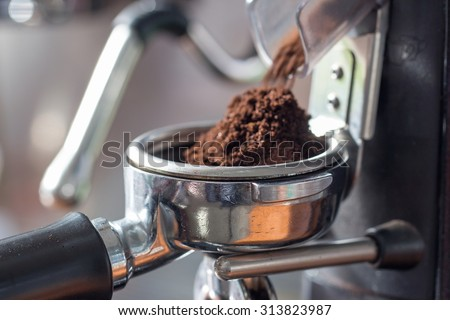 coffee grinder grinding freshly roasted coffee beans into a coffee powder - stock photo