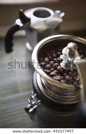 coffee grinder machine filled with coffee beans with italian mocha in background, aroma of roasted coffee - stock photo