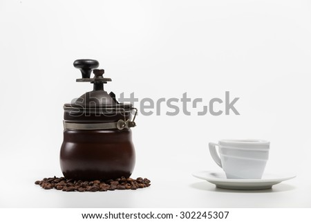 Coffee grinder with bean and coffee cup isolate on white in studio - stock photo