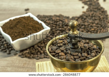 Coffee grinder with coffee beans, cup of coffee and ground coffee in bowl on wooden table - stock photo