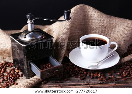 Coffee grinder with coffee beans on brown wooden background - stock photo