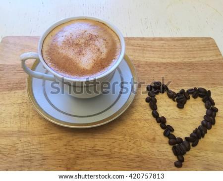 Coffee & heart. Coffee beans makes coffee Heart. Coffee & beans on wooden table, coffee cup & coffee beans background, coffee background with beans, colorful design coffee & coffee beans, coffee art - stock photo