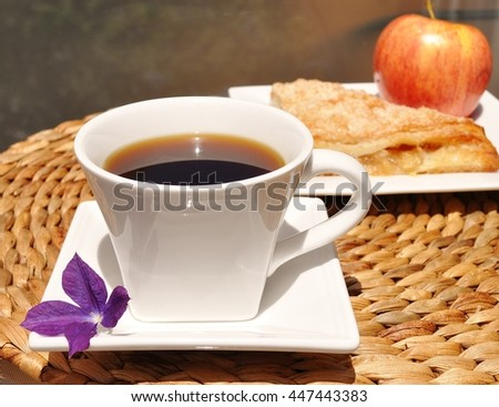 Coffee in a white cup with a purple flower on the side. Apple French pastry turnover and apple in the background - stock photo