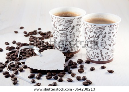 Coffee in paper cups with coffee beans and white heart  - stock photo