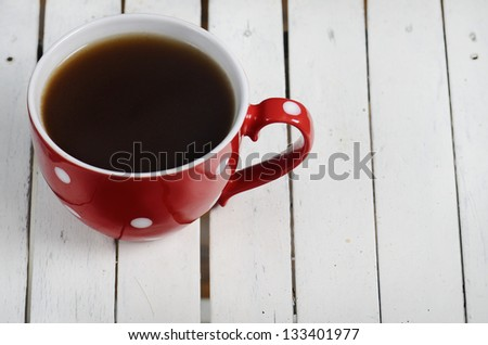Coffee in vintage red cup on wooden background - stock photo