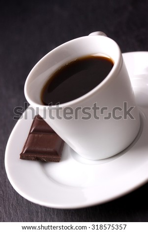 Coffee in white ceramic cup with chocolate on dark background