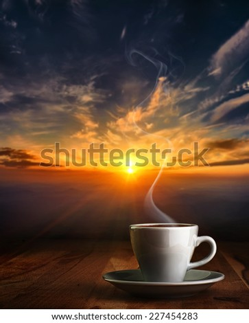 Coffee in white pottery cup on old wooden table with blurred image of  sunset or sunrise  - stock photo