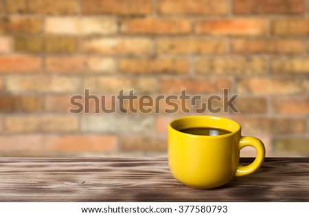 Coffee in yellow cup on wooden table opposite a defocused brick wall for background. Collage. Selective Focus. - stock photo