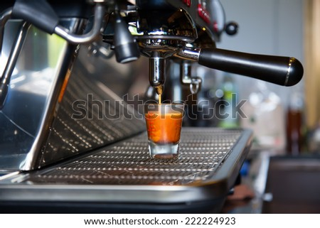 Coffee is pouring a glass of coffee machines. - stock photo