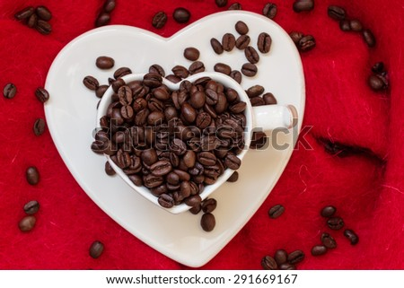 Coffee klatsch java concept. Heart shaped white cup filled with roasted coffee beans on red cloth background - stock photo