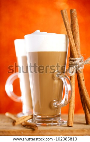 coffee latte with cinnamon sticks, red glitter backdrop, shallow dof - stock photo