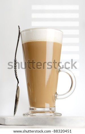 coffee latte with frothy milk in tall glass, gobo light, white wood - stock photo