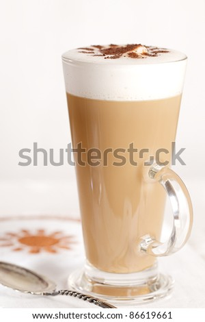 coffee latte with frothy milk in tall glass, rustic style, white wood - stock photo