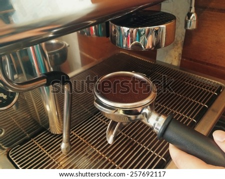 Coffee maker pouring fresh espresso coffee in a cup. Food and beverage - stock photo