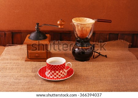 Coffee mill and a cup of coffee on the table - stock photo