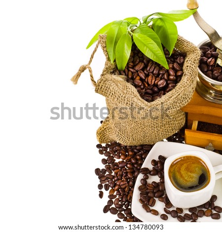 coffee mill, canvas bag with coffee beans decorated with green leaves and a cup of black coffee isolated on white background - stock photo