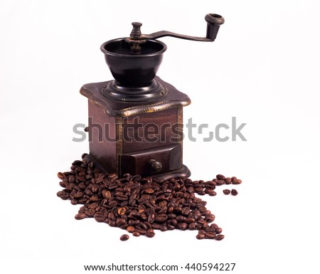Coffee mill, coffee grinder. Many coffee beans in the background. Texture of the coffee beans on a white background. Smelly, saturated brown arabic coffee beans - stock photo